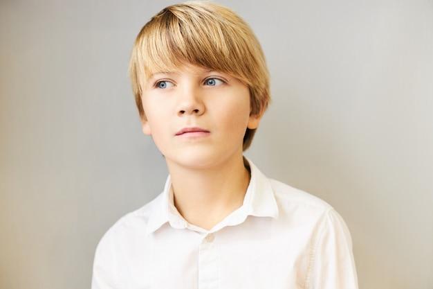 Retrato isolado de um menino branco espantado com franjas e olhos azuis desviando o olhar com uma expressão pensativa misteriosa, imerso em pensamentos, pensando, tendo uma ideia ou fazendo um plano, posando para uma parede em branco