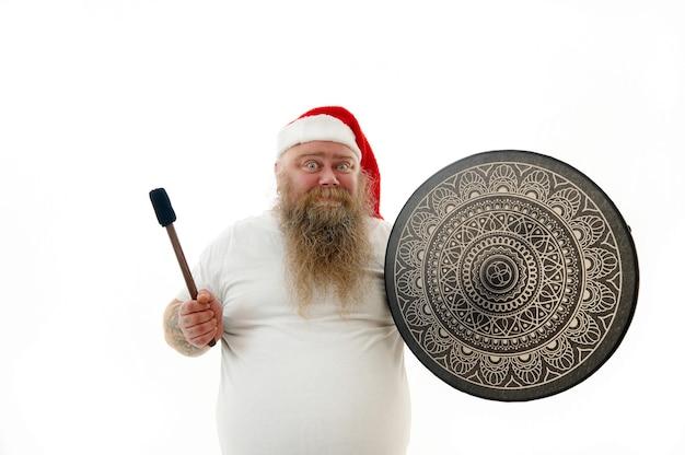 Retrato isolado de um xamã homem sorridente com peso excessivo e braços tatuados no chapéu de papai noel, segurando um pandeiro xamã, expressando emoção.