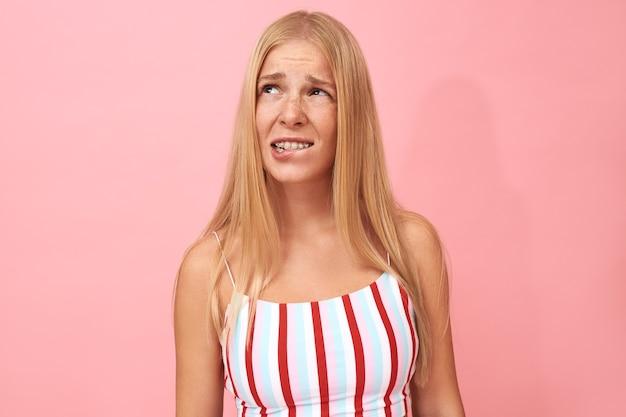 Retrato isolado de uma jovem frustrada com uma blusa listrada, olhando para cima com uma expressão facial perplexa, sentindo-se desconfortável