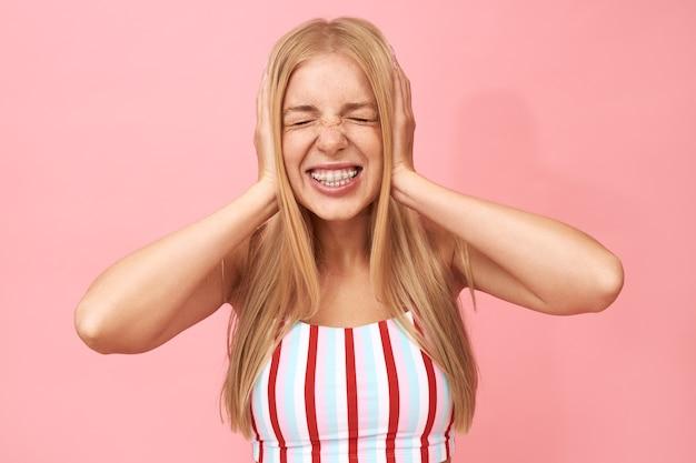 Retrato isolado de uma jovem mulher irritada e infeliz com cabelo longo e reto e aparelho cerrando os dentes, mantendo os olhos fechados e cobrindo as orelhas com as mãos
