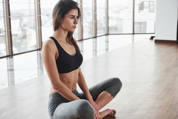 Retrato isolado jovem bonito relaxado senta-se no chão no ginásio com grandes janelas