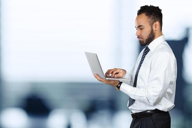 Retrato isolado jovem preto masculino segurando laptop