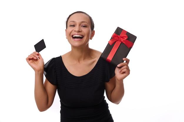 Retrato isolado no fundo branco com espaço de cópia de uma atraente mulher afro-americana rindo vestida de preto, segurando um cartão de crédito de desconto e uma caixa de presente, olhando para a câmera. conceito de black friday