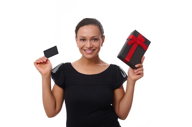 Retrato isolado no fundo branco com espaço de cópia de uma mulher afro-americana sorridente atraente vestida de preto, segurando um cartão de crédito de desconto e uma caixa de presente, olhando para a câmera. conceito de black friday