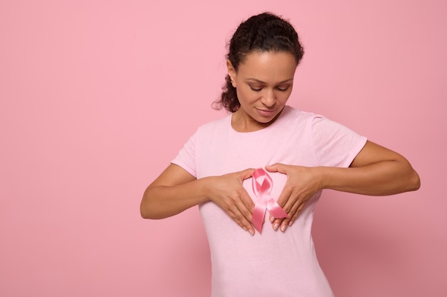 Retrato isolado no fundo colorido de uma mulher afro-americana em uma camiseta rosa, colocando as mãos no peito em forma de coração com uma fita de cetim rosa no centro. dia mundial da conscientização do câncer.