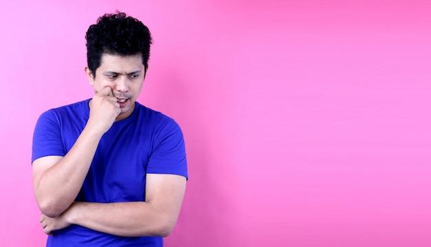 Retrato jovem ásia homem tendo dúvidas e com a expressão do rosto confuso sobre fundo rosa no estúdio