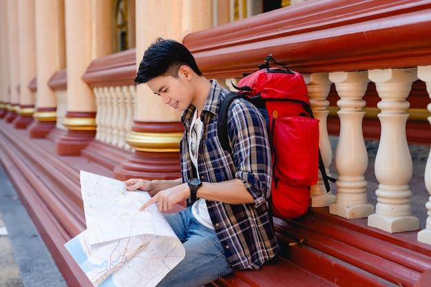 Retrato jovem asiático mochileiro masculino sentado e usar a ponta do dedo no mapa de papel para verificar a direção e sorrir no belo templo tailandês