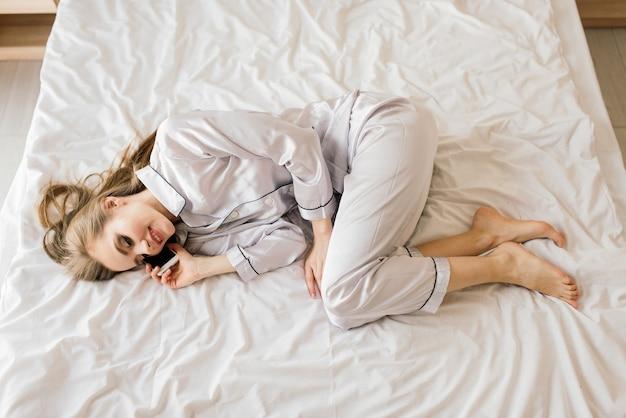 Retrato jovem bela mulher sorridente deitada na cama, bebendo seu café da manhã sonhando. cara feliz