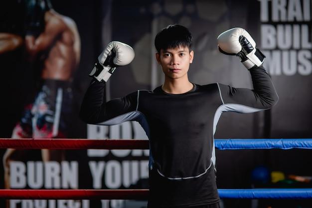 Retrato jovem bonito em roupas esportivas e luvas de boxe brancas em pé, levantar os braços para posar na tela no ginásio de fitness, aula de boxe de treino de homem saudável.