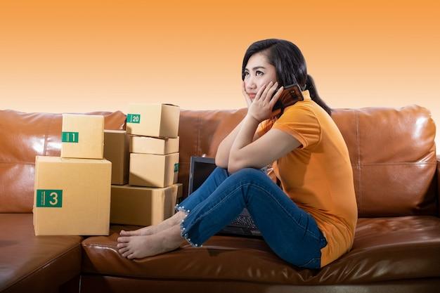 Retrato jovem entediada está sentada no sofá no quarto dela, as mulheres usavam o telefone móvel em fundo laranja, uma senhora está entediada porque as vendas caíram do conceito de meta de vendas