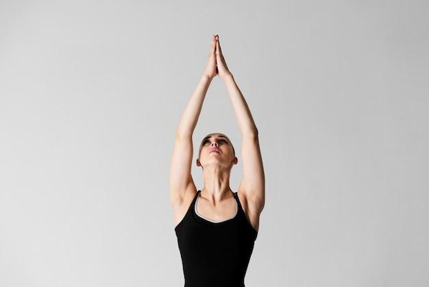 Retrato jovem fêmea com as mãos unidas no ar