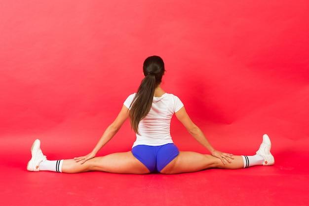 Retrato jovem fitness feminino fazendo salto dividido