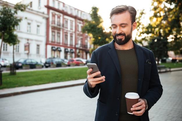 Retrato, jovem, homem, segurando, telefone móvel