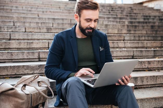 Retrato, jovem, homem, trabalhando, laptop