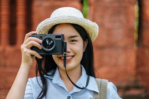 Retrato jovem mochileiro feminino usando chapéu viajando em local antigo, ela sorrindo e usando a câmera tirando foto com felicidade, copie o espaço