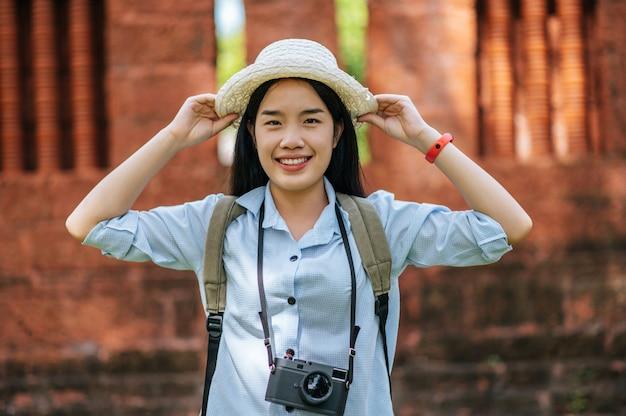 Retrato jovem mochileiro feminino usando chapéu, viajando em um local antigo, ela sorrindo e olhando para a câmera com felicidade, copie o espaço