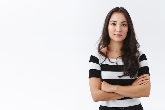 Retrato jovem morena de leste asiático em camiseta listrada, braços cruzados no peito em pose confiante, profissional e determinada, sorrindo confiante, fundo branco em pé motivado