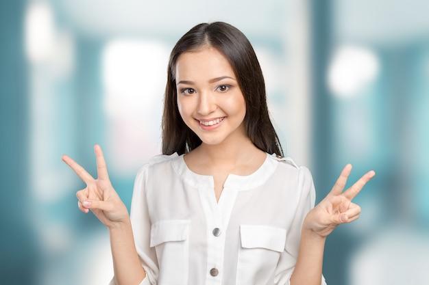 Retrato, jovem, morena, sorrindo, mostra, sinal vitória