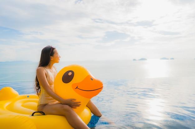 Retrato, jovem, mulher asian, ligado, inflável, flutuador, pato amarelo, ao redor, piscina ao ar livre, em, hotel, e, recurso
