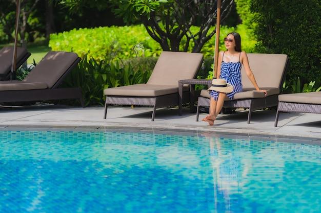 Retrato, jovem, mulher asian, relaxe, sorrizo, feliz, ao redor, piscina exterior, em, hotel, recurso, com, mar, oceânicos, vista