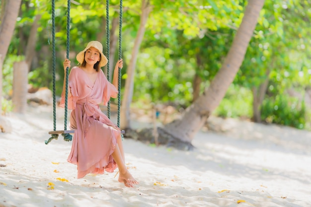 Retrato, jovem, mulher asian, sentando, ligado, balanço, corda, e, mar, ao redor, praia, mar, oceânicos, coqueiro, palma