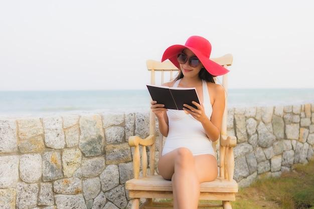 Retrato, jovem, mulher asiática, ler livro, ao redor, praia, mar, oceano