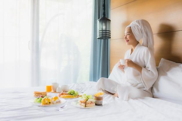 Retrato jovem mulher asiática na cama com café da manhã no quarto