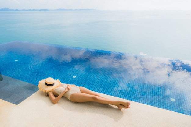 Retrato jovem mulher asiática relaxar sorriso feliz ao redor da piscina no hotel e resort