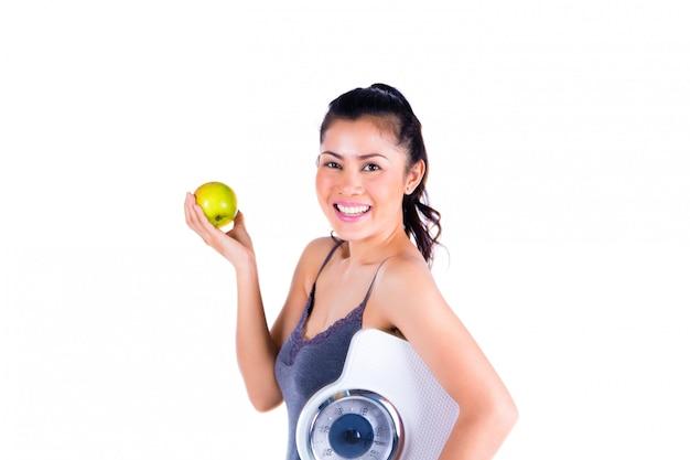 Retrato, jovem, mulher asiática, segurando, maçã, e, escala
