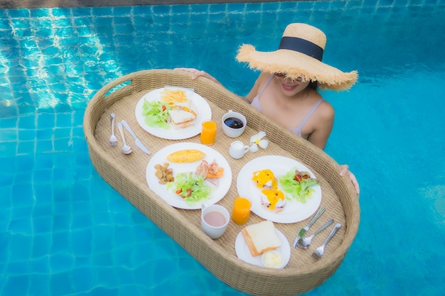 Retrato jovem mulher asiática sorriso feliz desfrutar com flutuante bandeja de café da manhã na piscina no hotel