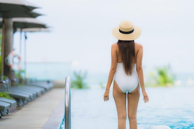 Retrato jovem mulher asiática sorriso feliz relaxar ao redor da piscina no hotel resort