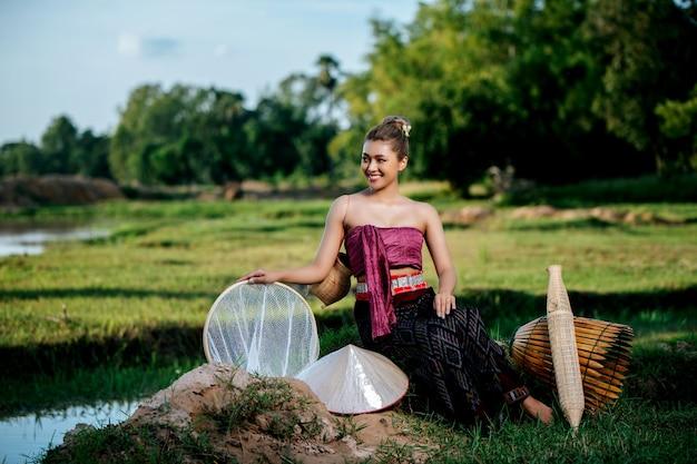 Retrato jovem mulher bonita asiática em lindas roupas tradicionais tailandesas no campo de arroz, ela sentada perto de equipamentos de pesca