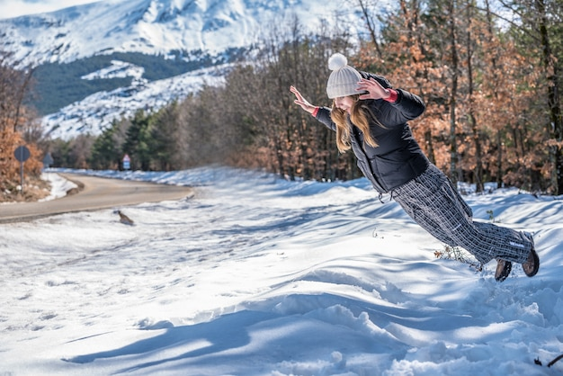Retrato jovem mulher bonita pulando na neve em uma estrada no inverno