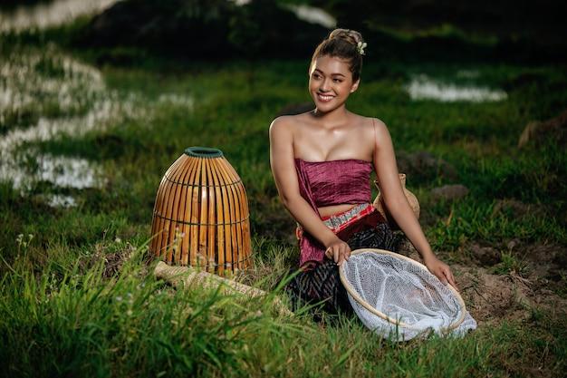 Retrato jovem mulher muito asiática com lindas roupas tradicionais tailandesas no campo de arroz, sentada perto de equipamentos de pesca
