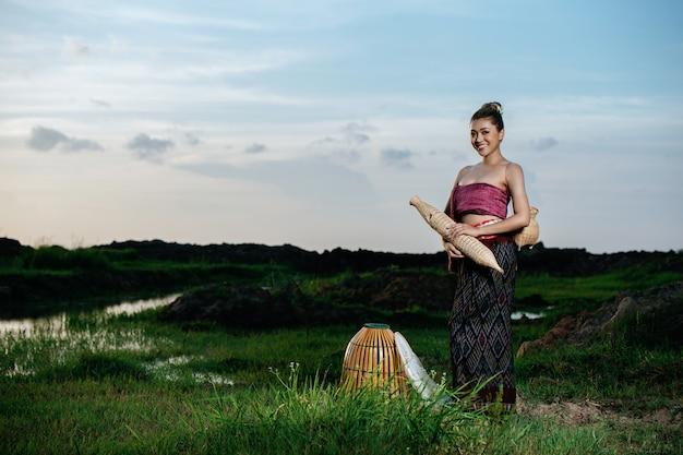 Retrato jovem mulher muito asiática em lindas roupas tradicionais tailandesas no campo de arroz, ela de pé e segurar o equipamento de pesca