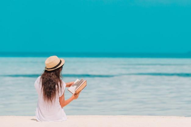 Retrato, jovem, mulher, relaxante, praia, lendo um livro