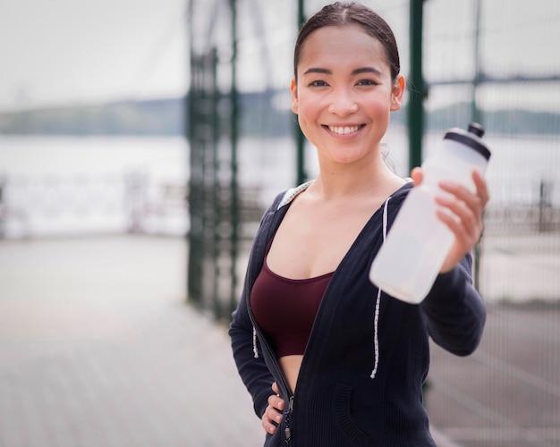 Retrato, jovem, mulher, segurando, garrafa água