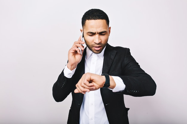 Retrato jovem ocupado na camisa branca, jaqueta preta, falando no telefone e olhando para o relógio. homem de negócios elegante, ocupado, tempo para trabalho, reunião, negócios modernos.