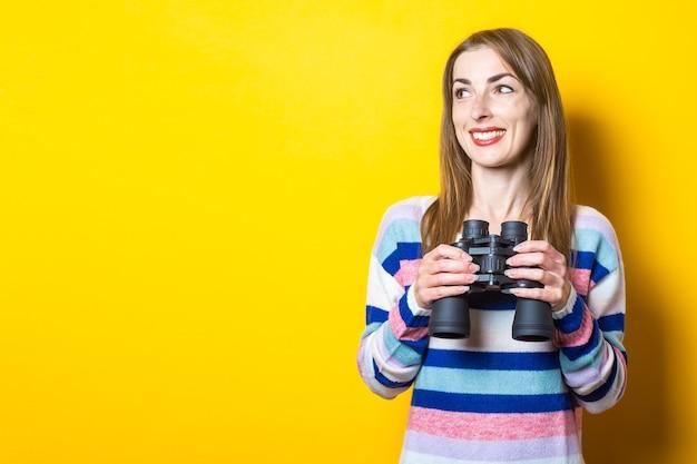 Retrato jovem olha através de binóculos