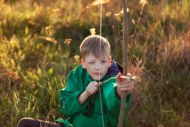 Retrato jovem rapaz, atirar com arco artesanal e flecha no alvo no pôr do sol, verão ao ar livre.