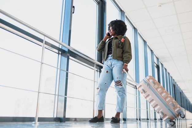 Retrato lateral de corpo inteiro de jovem negra caminhando com uma mala no aeroporto