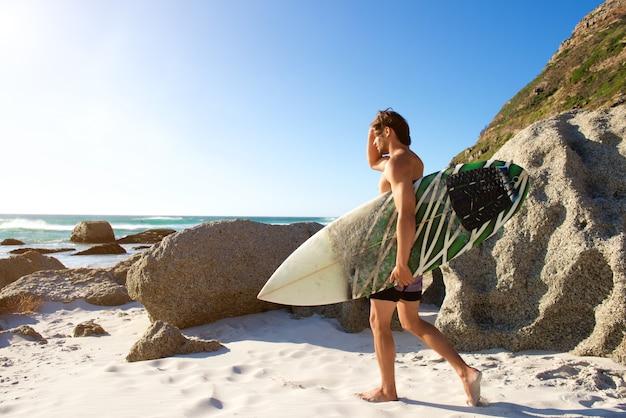 Retrato lateral, de, homem jovem, com, surfboard, andar praia