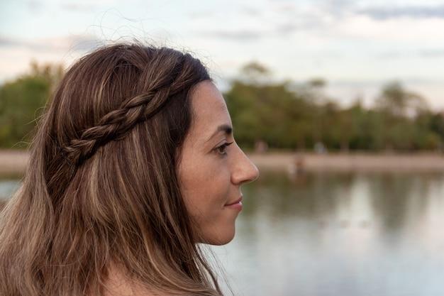 Retrato lateral de mulher com fundo de um lago no outono. foco seletivo.