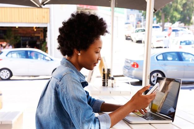 Retrato lateral, de, mulher, usando, cellphone, com, laptop