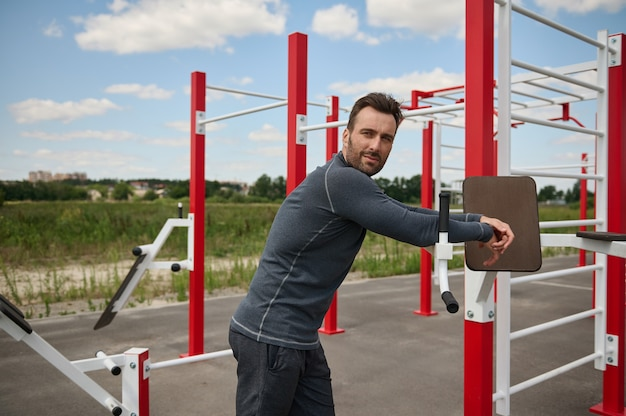 Retrato lateral de um atleta europeu atraente e bonito de construção muscular caucasiana, olhando para longe, descansando após o treino no fundo das barras transversais