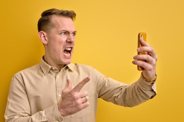Retrato lateral de um homem irritado repreendendo alguém através do smartphone