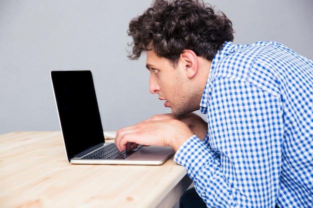 Retrato lateral de um homem usando um laptop