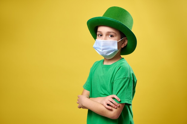 Retrato lateral de um menino com chapéu irlandês verde e máscara médica protetora posa para a câmera com os braços cruzados