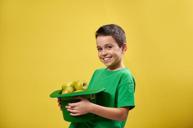 Retrato lateral de um menino sorridente segurando um chapéu de duende cheio de maçãs verdes