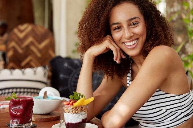 Retrato lateral de uma jovem atraente, alegre, de pele escura, com penteado espesso, que come a sobremesa no restaurante com uma expressão alegre, tem férias de verão em um país tropical